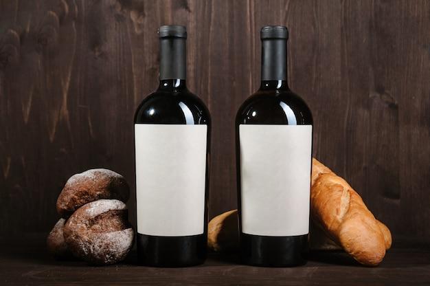 Composición de vino blanco con pan, dos botellas y copa de vino en sala de madera