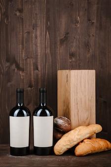 Composición del vino con pan, dos botellas en caja y copa de vino en la mesa de madera