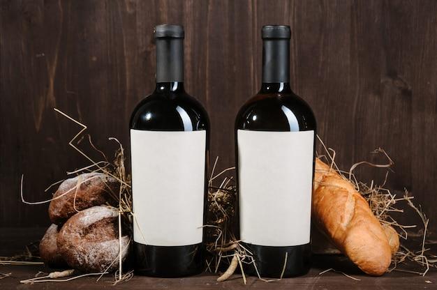 Composición del vino con pan, dos botellas y copa de vino en la mesa de madera marrón