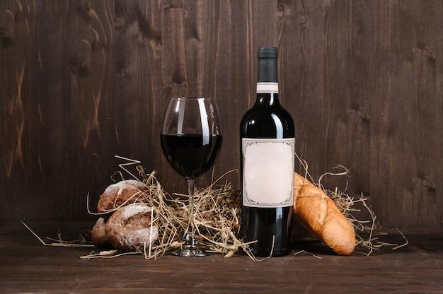 Composición de vino tinto con botella de pan y copa de vino en la mesa de madera