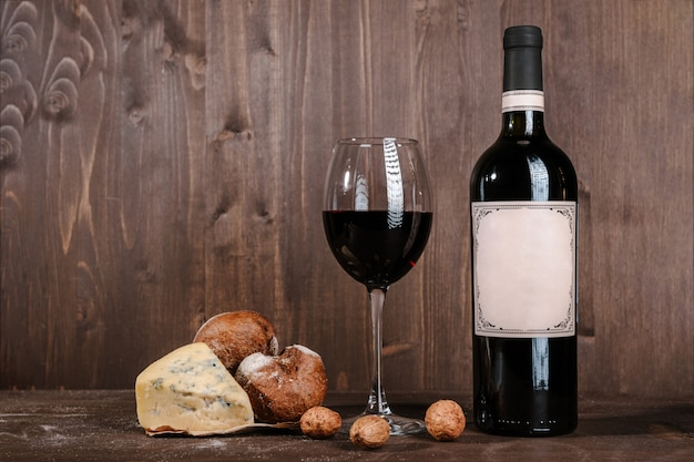 Composición de vino tinto con pan, dos botellas en caja y copa de vino en mesa de madera