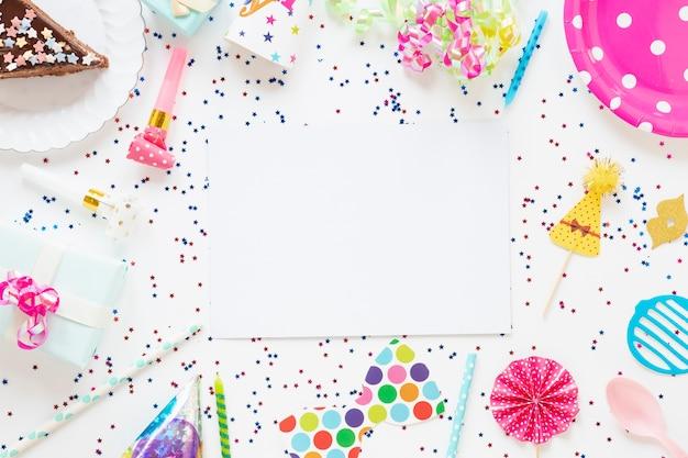 Composición de la vista superior de artículos festivos de cumpleaños con tarjeta vacía