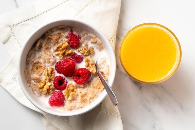 Composición de la vista superior de cereales tazón de fuente saludable con jugo de naranja