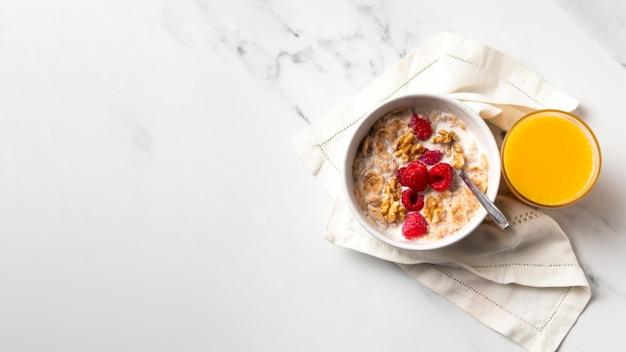 Composición de la vista superior de cereales de tazón saludable con jugo de naranja con espacio de copia