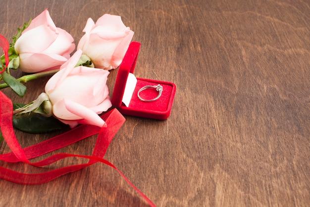 Composición de la vista superior con rosas y anillo de compromiso.