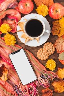 Composición de vista superior con taza de café y teléfono inteligente