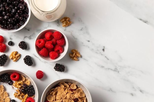 Composición de la vista superior de tazón de cereales saludables con bayas con espacio de copia