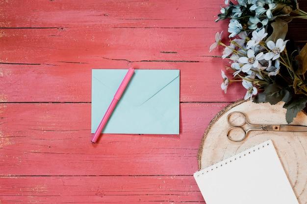 Composiciones de boda con sobre de invitación, flores, bolígrafo y tijeras sobre un fondo de madera rosa claro