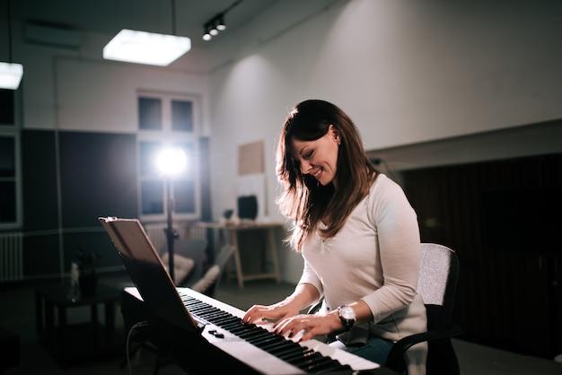 Compositor femenino tocando el sintetizador de piano