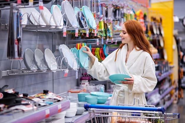 Compra femenina eligiendo platos en el supermercado, comparando los más hermosos. mujer en bata de baño en compras