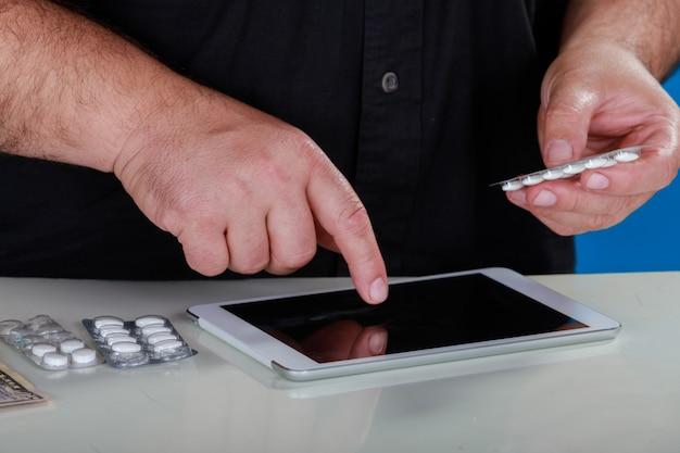 Compra de medicamentos a través de internet, manos masculinas con pastillas, muestra de medicamentos y orden de mecanografía