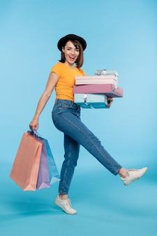 Comprador alegre joven en ropa casual llevando pila de regalos envueltos y montón de bolsas de papel mientras se va a casa después de la venta