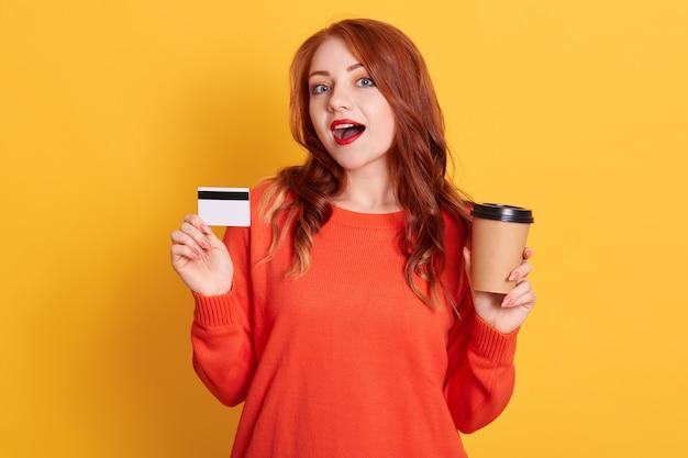 Comprador asombrado al encontrar una oferta en línea, sosteniendo café para llevar y tarjeta de crédito, ha sorprendido la expresión facial, dama con labios rojos y cabello ondulado
