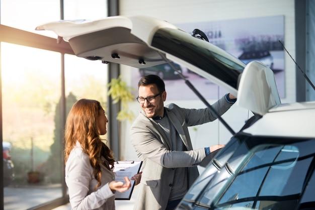 Comprador de automóviles probando el espacio del maletero de un automóvil nuevo en la sala de exposición del concesionario de vehículos local