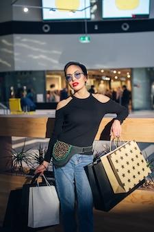 Comprador caminando en el centro comercial o centro comercial con bolsas de compras