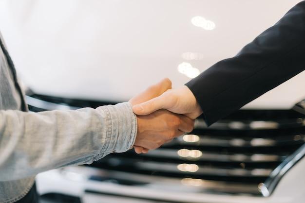 Comprador de coche un apretón de manos con el vendedor en el concesionario de automóviles delante del coche