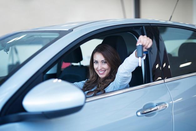 Comprador de coche feliz sentado en vehículo nuevo mostrando las llaves en la sala de exposición del concesionario