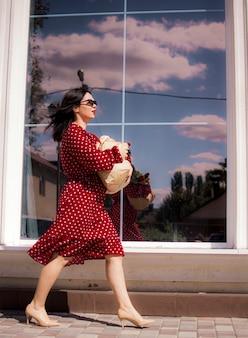 Comprador de comestibles feliz. retrato de hermosa mujer blanca tradicional en vestido rojo con bolsa de papel llena de comestibles.