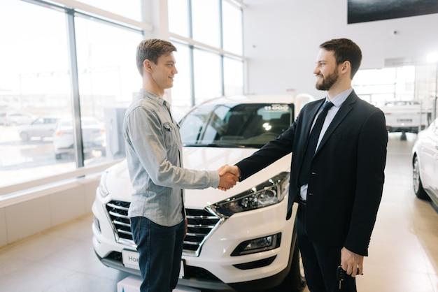 Comprador feliz de coche un apretón de manos con el vendedor en el concesionario de automóviles delante del coche