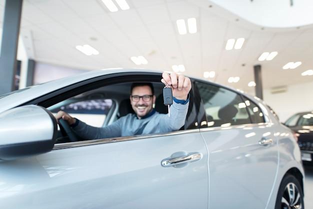 Comprador feliz sentado en un vehículo nuevo y sosteniendo las llaves del coche