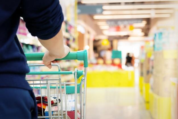 Comprador femenino con carro con movimiento borroso de grandes almacenes de supermercado