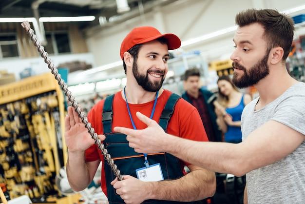 El comprador hace preguntas al vendedor sobre el taladro gigante.