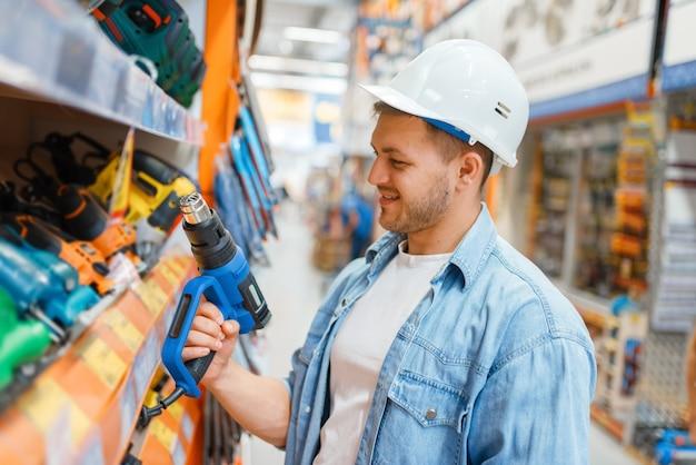 Comprador masculino eligiendo herramientas en ferretería. el cliente mira las mercancías en la tienda de bricolaje, compras en el supermercado del edificio