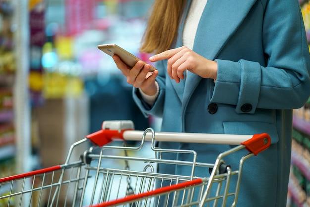 Compradora con carro en el pasillo de la tienda con lista de compras en el teléfono inteligente durante la compra de alimentos