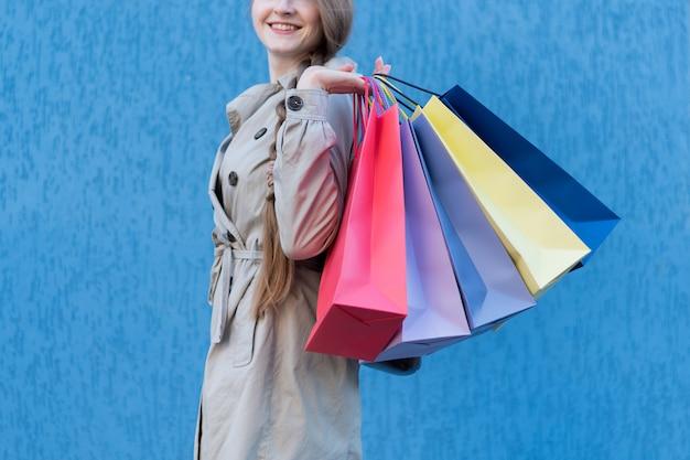 Compradora compulsiva joven feliz con bolsos coloridos