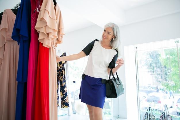 Compradora femenina alegre elegir vestido de fiesta, mirando por encima de la ropa en el estante en la boutique. mujer de compras en la tienda. concepto de consumismo