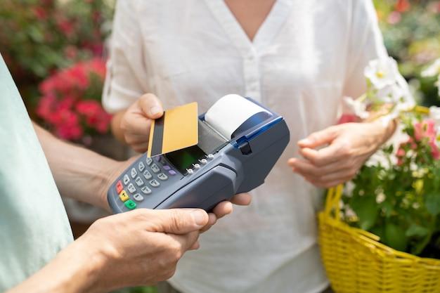 Compradora femenina contemporánea con tarjeta de crédito para pagar algunas flores frescas en macetas en el centro de jardinería contemporáneo