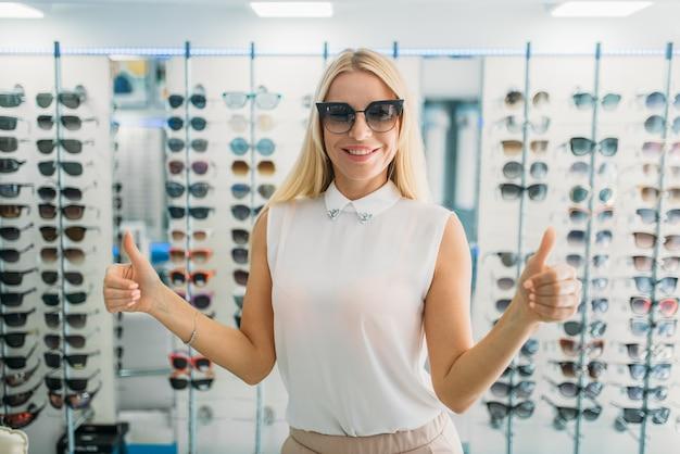 Compradora femenina se prueba gafas de sol en la tienda de óptica, escaparate con gafas. protección para los ojos de la luz solar en la tienda de gafas, concepto de cuidado de los ojos
