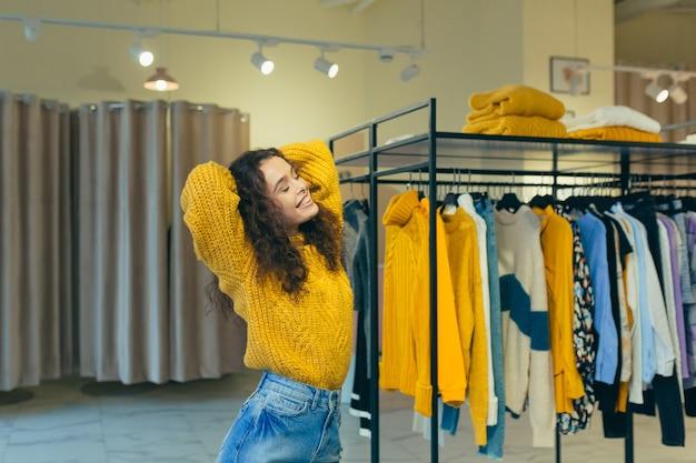 Compradora hermosa chica, probándose y comprando ropa hermosa y elegante en una boutique