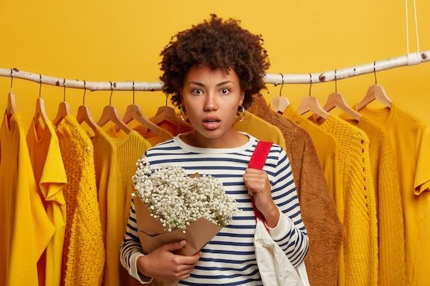 Compradora mujer emotiva mira fijamente con expresión asustada, reacciona ante los altos precios en la tienda, lleva una bolsa de compras en los hombros, se para contra el perchero
