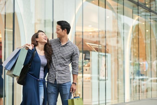 Compradores felices riendo sin preocupaciones en un centro comercial