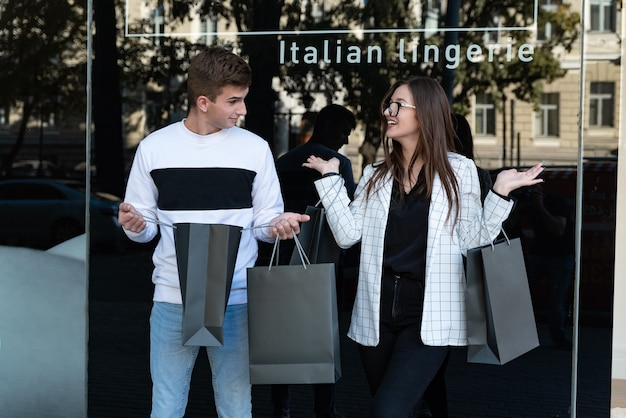 Compradores de la joven pareja con bolsas de la compra sobre fondo de escaparate. guy mira a su novia con sorpresa. viernes negro.