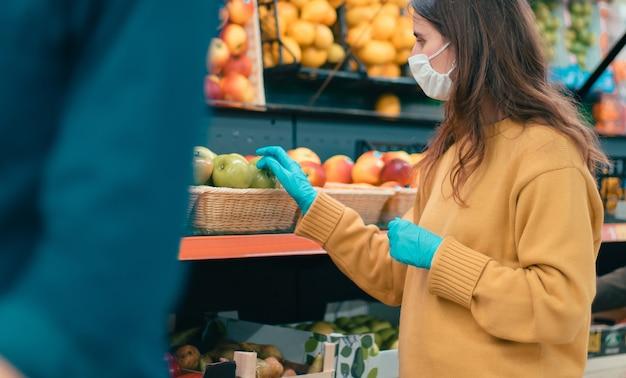 Compradores con máscaras protectoras que eligen fruta en el supermercado. coronavirus en la ciudad