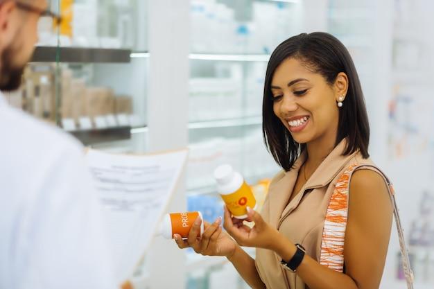 Comprando ambos. increíble mujer internacional manteniendo una sonrisa en su rostro mientras escucha al consultor