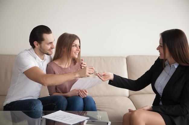 Comprando casa. joven pareja feliz recibiendo las llaves de su propio apartamento