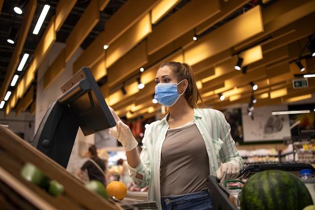 Comprar alimentos en un supermercado durante la pandemia mundial del virus corona
