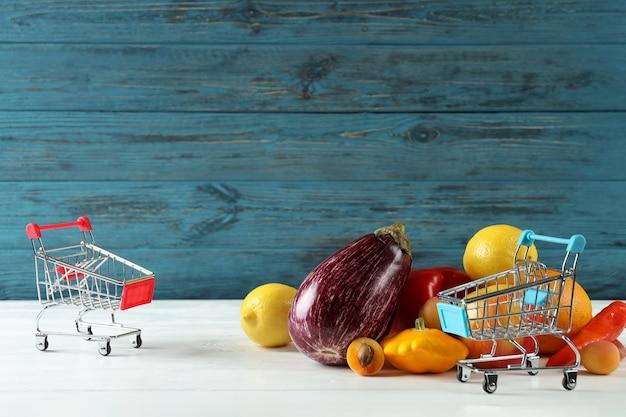 Comprar carros, verduras y frutas en mesa de madera