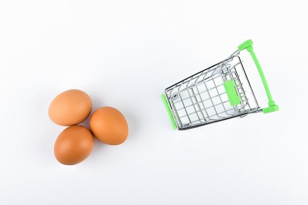Comprar huevos concepto comercial. tienda en linea. cesta y huevos en blanco