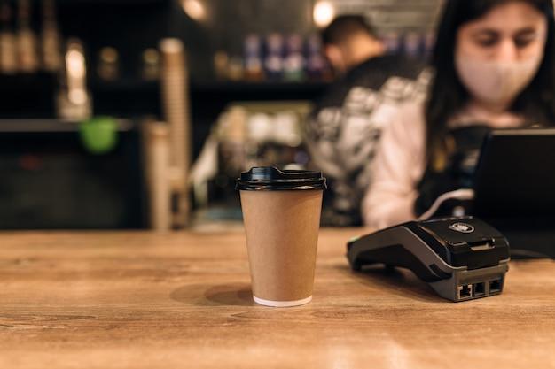 Comprar una taza de café en una cafetería, barista, terminal nfc. fondo borroso. foto de alta calidad