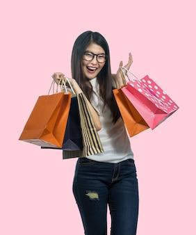 Compras asiáticas jovenes felices de la mujer en la sensación feliz y sostener la bolsa de papel del producto