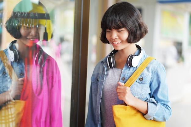 Compras asiáticas de la mujer con la bolsa de asas y el auricular que miran el paño en tienda