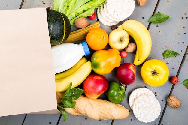 Compras de comestibles . bolsa de papel de diferentes alimentos en madera. endecha plana.