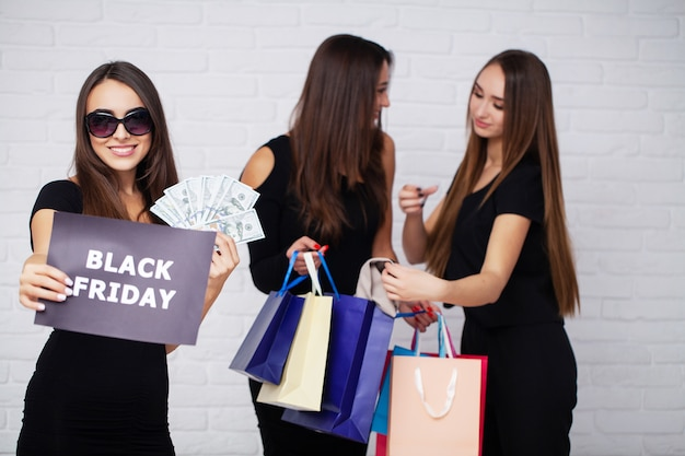 Compras. elegante mujer morena viste vestido negro con bolsas de compras, concepto de viernes negro