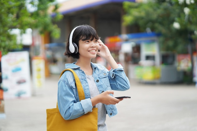 Compras felices de la mujer con escuchar la música en smartphone y sostener la bolsa de asas