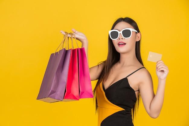 Compras hermosa mujer con gafas con una tarjeta de crédito de oro con una bolsa de papel de colores en un amarillo.
