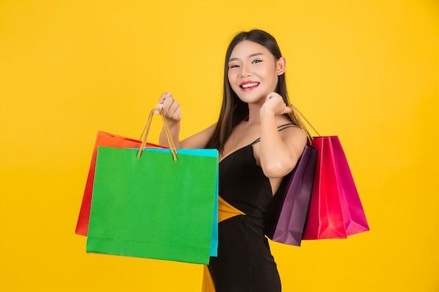 Compras hermosa mujer sosteniendo una bolsa de papel de colores en un amarillo.